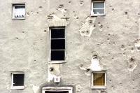 alte Hausfassade in Berlin mit bröckelndem Putz und Einschusslöchern aus dem zweiten Weltkrieg
