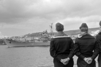 Soldaten der DDR-Volksmarine nehmen Aufstellung, im Hintergrund ein Schiff im Hafen