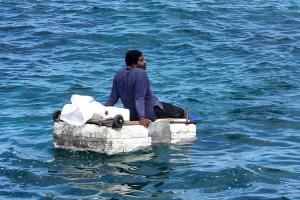 Mann auf einem selbstgebauten Floß