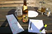 Reiseplanung mit einer Landkarte, einem Notizblock und einer Flasche Bier