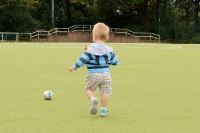 Früh übt sich: Kleiner Junge mit anderthalb Jahren auf dem Fußballplatz. Lass rollen...